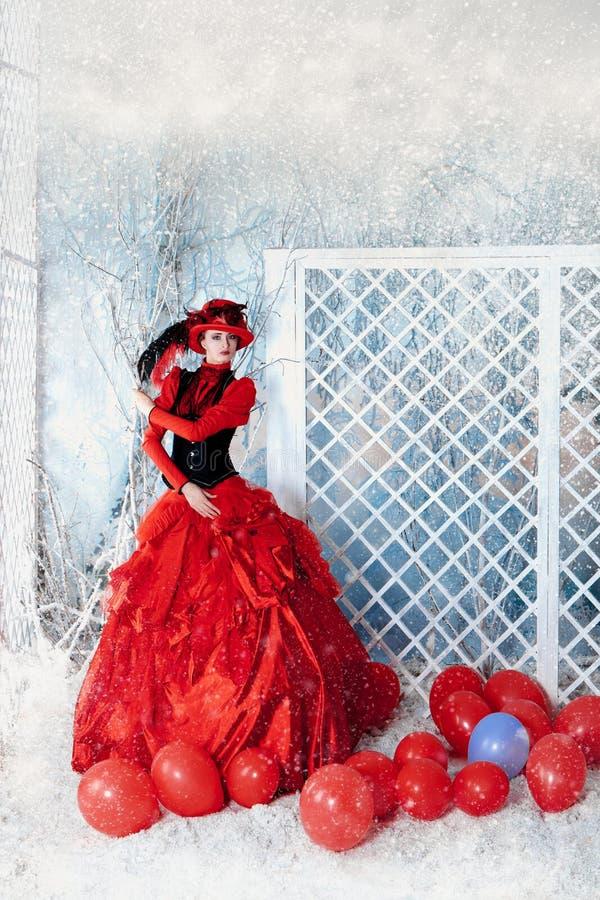 Modieuze vrouw in het rode overvloedige kleding stellen stock fotografie