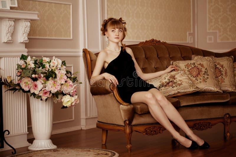 Modieuze vrouw in luxueuze binnenlands royalty-vrije stock afbeelding