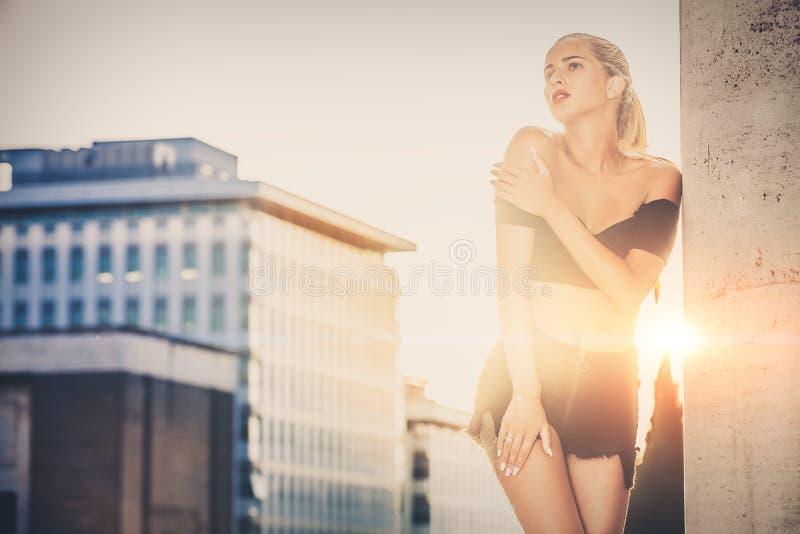 Modieuze vrouw met stedelijke erachter zonsondergang Vrijetijdskleding, blondehaar en sensuele houding stock foto's