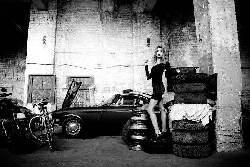 Modieuze vrouw in retro garage stock afbeeldingen