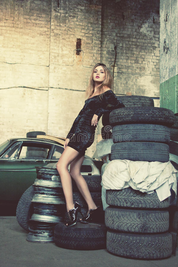 Modieuze vrouw in retro garage stock fotografie