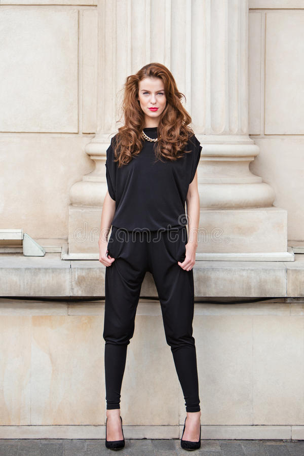 Modieuze vrouw in rugloze jumpsuit stock foto