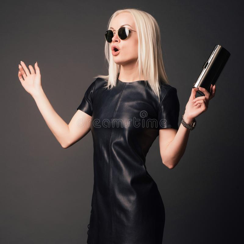 Modieuze vrouw in zwarte leerkleding met klein zilveren zak en horloge Het concept van de manier royalty-vrije stock afbeeldingen