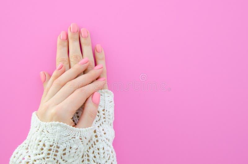 Modieuze in vrouwelijke roze manicure Mooie jonge vrouwen` s handen op roze achtergrond Basis, natuurlijk, eenvoudig en stock foto