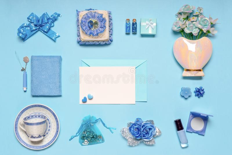 Modieuze vrouwelijke toebehoren, bloemen, schoonheidsmiddelen, giften en decoratieve punten in blauwe pastelkleuren op blauwe ach royalty-vrije stock foto's