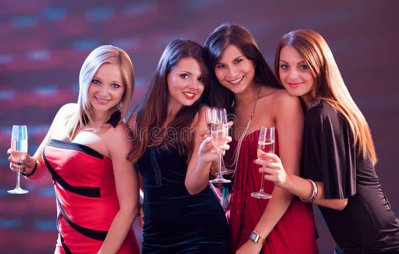 Modieuze vrouwen die met champagne roosteren stock foto