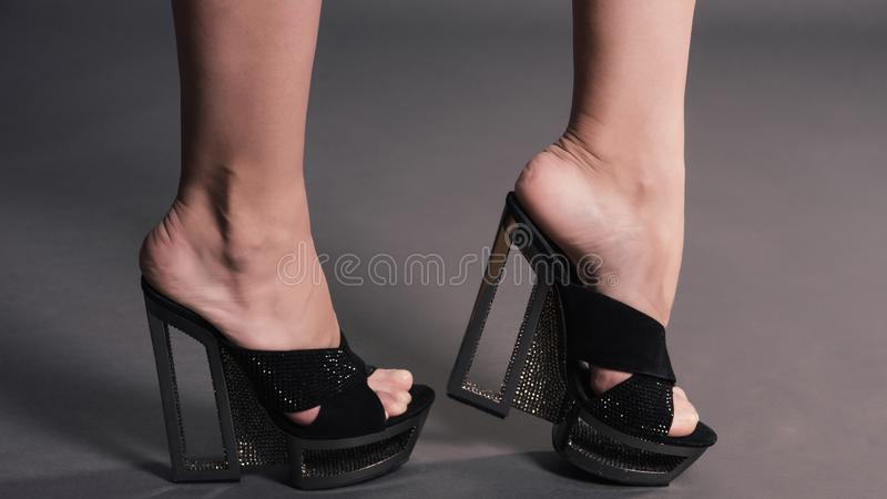 Modieuze vrouwen lange benen in schoenen van legging de zwarte modieuze hoge hielen met bergkristallen royalty-vrije stock fotografie