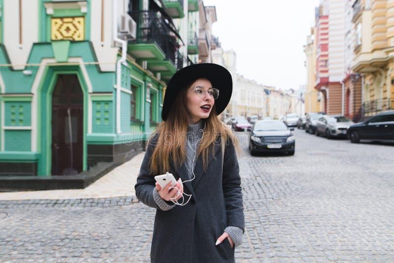 Modieuze vrouwentoerist die door de straten van de het oude stad en glimlachen wandelen Een meisje die langs de straten lopen stock foto