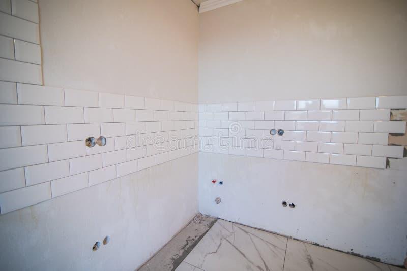 Modieuze in witte keramische tegel met een afkanting op de keukenmuur stock afbeelding