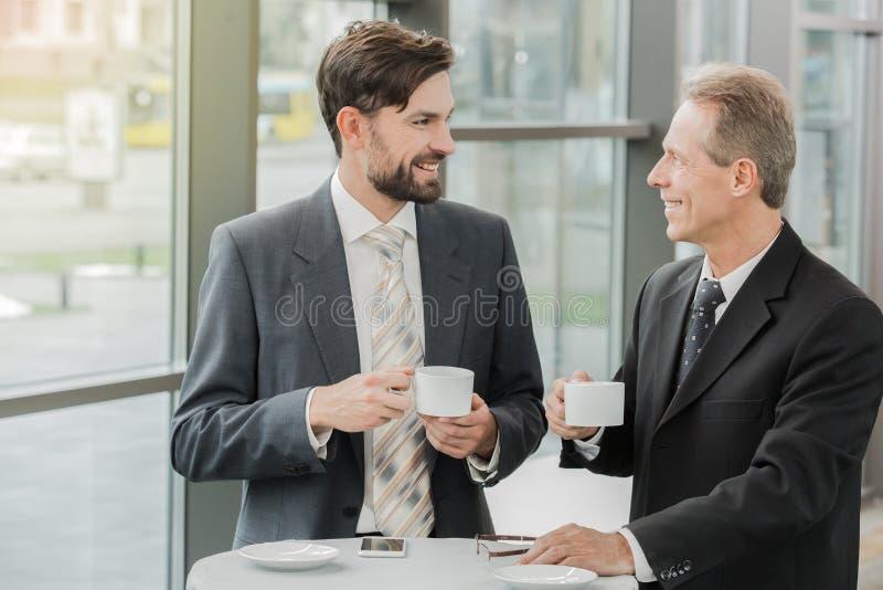 Modieuze zakenlieden die in bureau werken stock fotografie