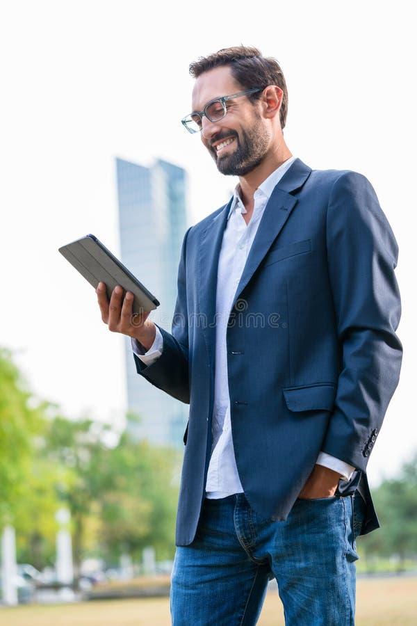 Modieuze zakenman die digitale tablet bekijken royalty-vrije stock afbeelding