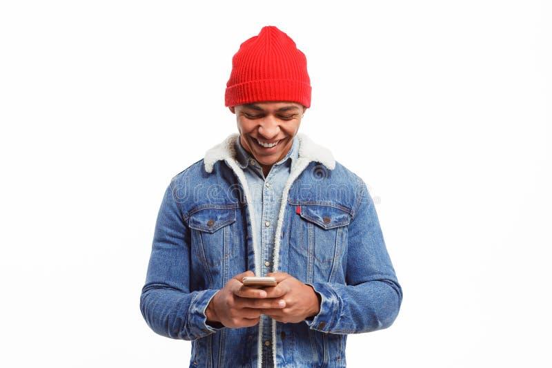Modieuze zwarte die mens met smartphone wordt opgewekt stock foto