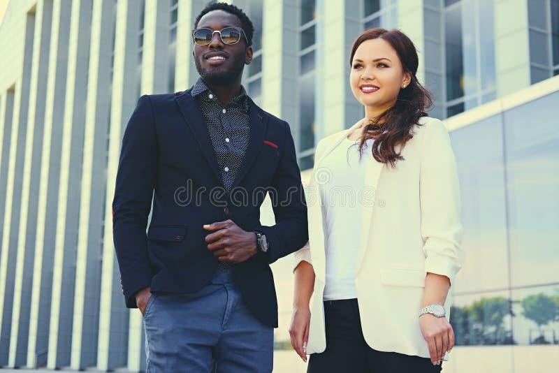 Modieuze Zwarte mens en Kaukasisch wijfje binnen de stad in royalty-vrije stock foto