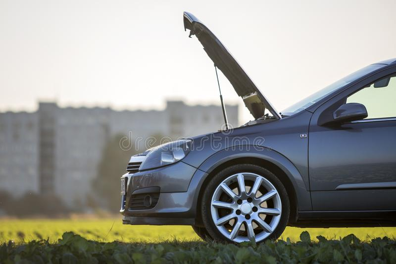 Modified image of a fictional non existent car. Car with open hood on empty gravel field road on blurred bright sky copy space. Background. Transportation stock photo