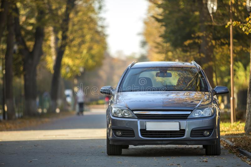 Modified image of a fictional non existent car. Car parked in quiet area on asphalt road on blurred green and yellow trees bokeh. Background on bright sunny day royalty free stock photos