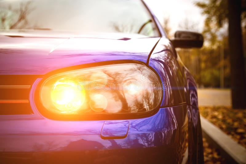 Modified yellow xenon headlights of blue modern car. Lowrider with air suspension Parked in the park royalty free stock image