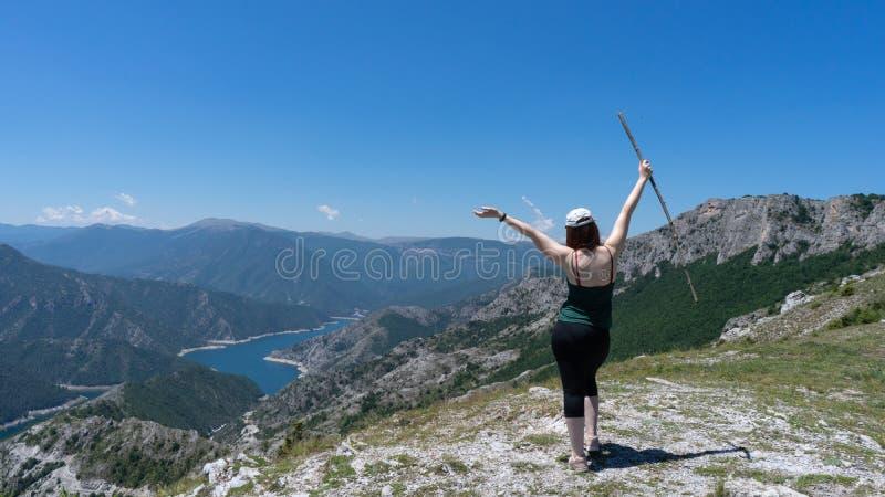 Modig flicka som erövrar bergmaxima av berg Lycklig frihetsfotvandrare med hatten och öppna armar som går med träpinnen, anseende arkivfoto
