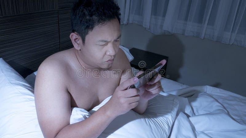 Modig hemfallen manlig spela lek på den smarta telefonen på säng på midnatt royaltyfri foto