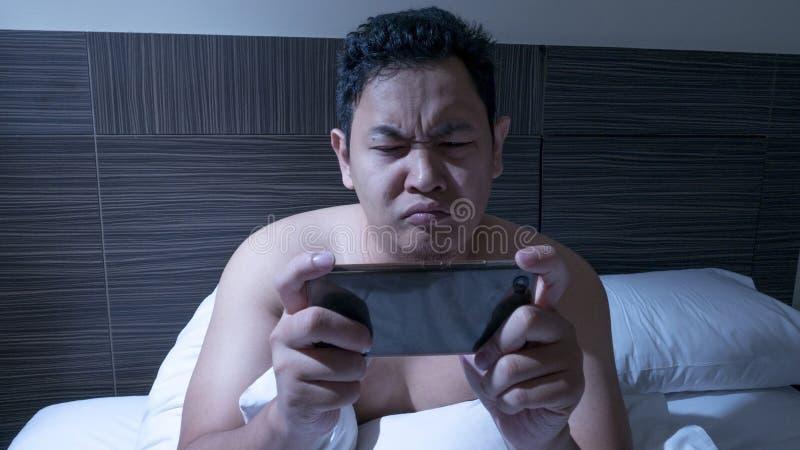 Modig hemfallen manlig spela lek på den smarta telefonen på säng på midnatt arkivbild