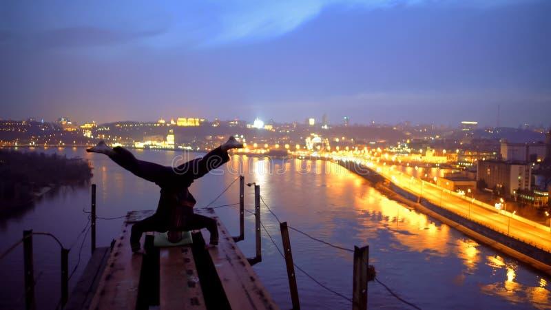Modig idrottsman nendanandehuvudstående på kanten av bron, adrenalin och sportar royaltyfria foton