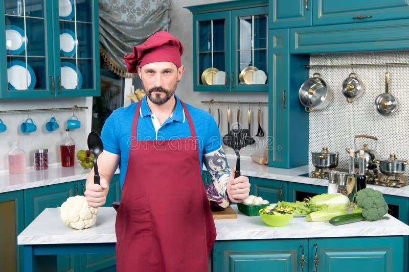 """Modig kock med skedar i händer Kock som är klar för ttlen för matbÑ"""" arkivfoto"""