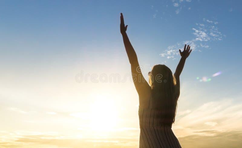 Modig lycklig ung kvinna som lyfter händer upp i luften fotografering för bildbyråer
