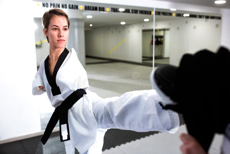 Modig och mentalt stark ung kvinna med fysiskt handikapp som utbildar hårda utförande kampsporter royaltyfri bild