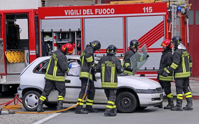 Modiga brandmän avlöser ett sårat efter en vägolycka royaltyfria foton