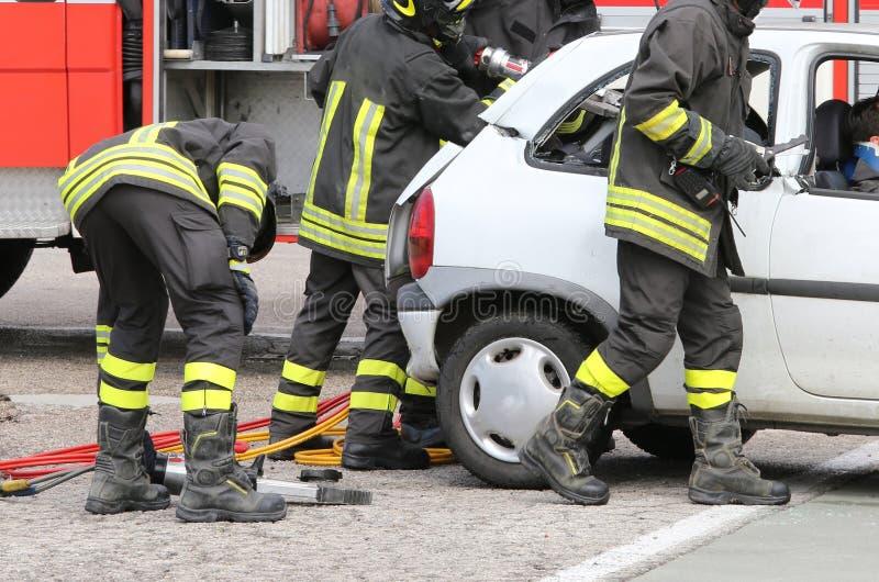 Modiga brandmän avlöser ett sårat efter en vägolycka royaltyfri bild