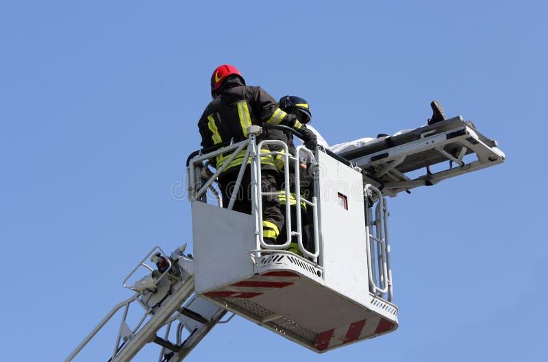 Modiga brandmän på buren för brandlastbil med båren royaltyfria foton
