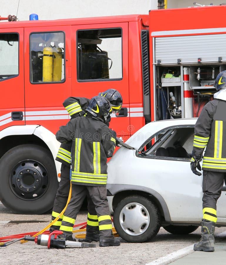 Modiga brandmän som klipps av bilen med sax för att frigöra det sårat royaltyfria bilder