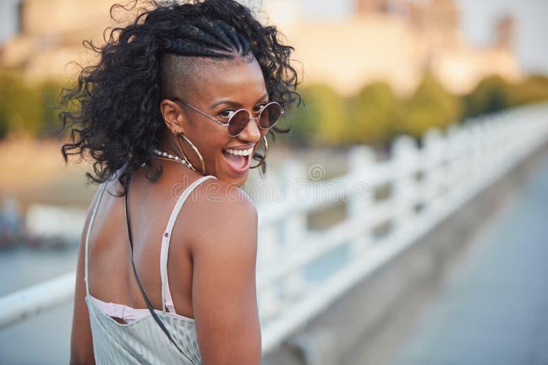 Modische Frau in gestreiftem Unterhemd und in der Sonnenbrille, drehend lizenzfreies stockbild