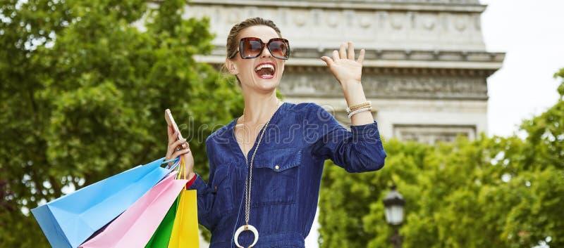 Modische Frau mit den Einkaufstaschen, die in Paris, Frankreich handwaving sind lizenzfreie stockfotografie