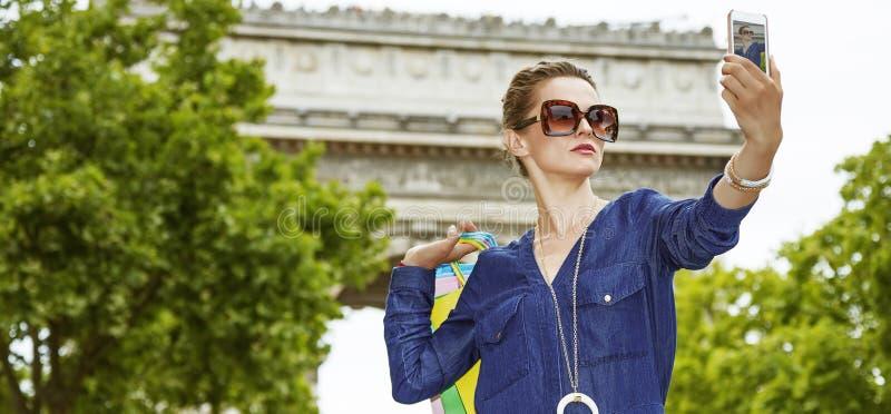 Modische Frau mit den Einkaufstaschen, die selfie in Paris, Frankreich nehmen stockfotos