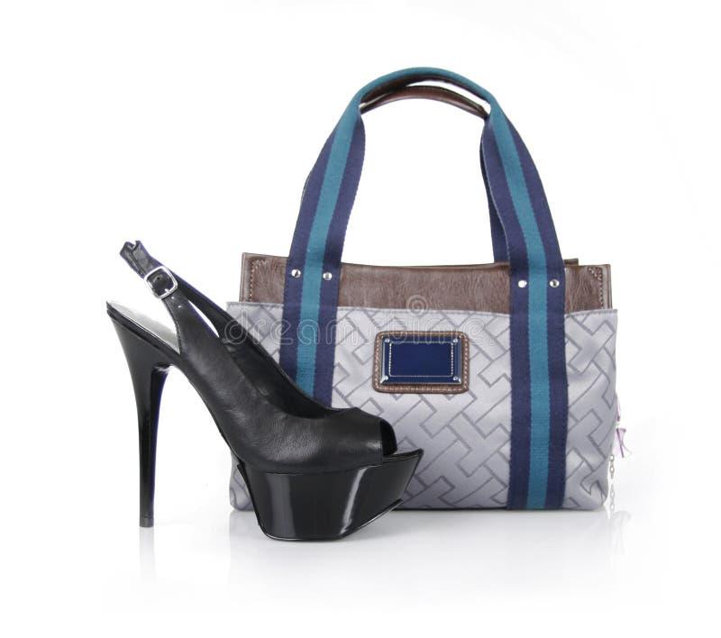 Modische Handtasche und schwarzer Schuh stockfotos