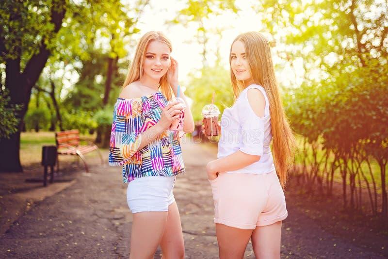 Modische jugendlich Frauen mit Getränken lizenzfreie stockbilder