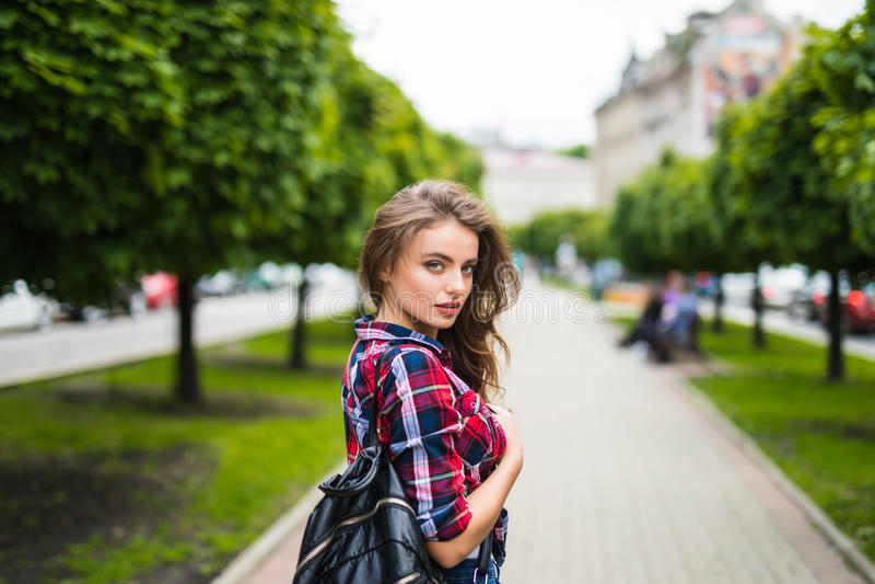 Modische junge Frau des Modeporträts mit Rucksack im Stadt Simmer lizenzfreie stockfotos