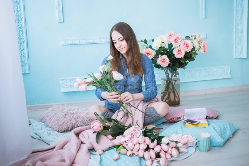 Modische junge Frau, die auf dem Boden, Blumenblumenstrauß von den rosa Tulpen im hellen sonnenbeschienen Raum mit blauen Wänden  stockbild