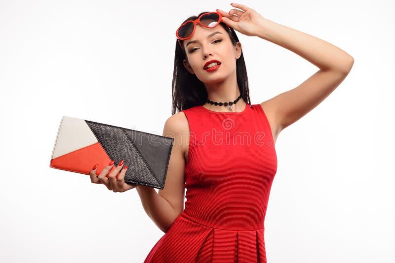 Modische junge Frau im roten Kleid und in der Kupplung hält an zur Sonnenbrille in Form des Herzens lizenzfreie stockfotografie