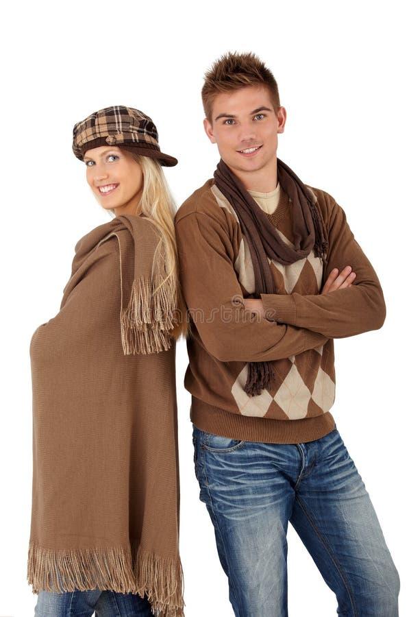 Modische junge Paare, die in der Winterkleidung aufwerfen stockbild