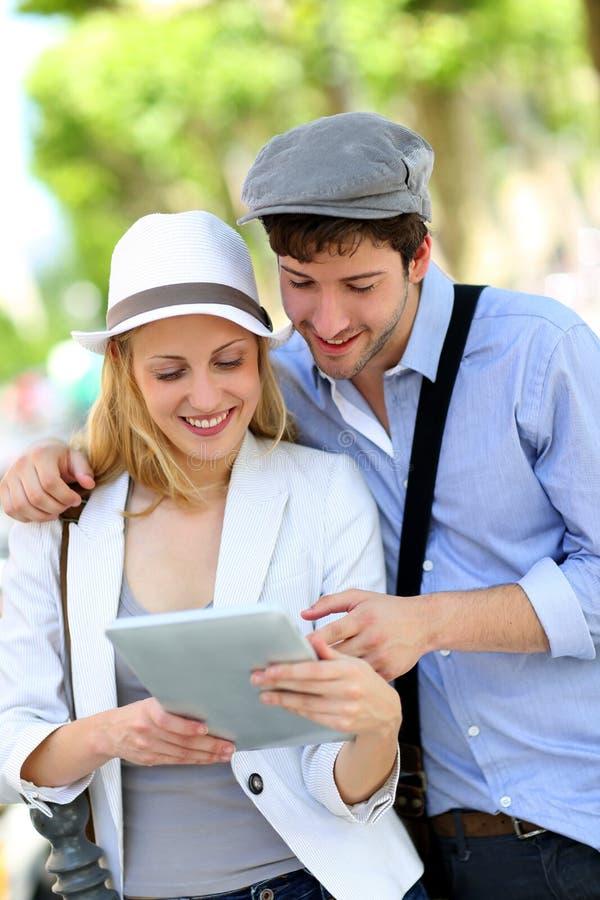 Modische junge Paare, die draußen unter Verwendung der Tablette hängen lizenzfreies stockbild