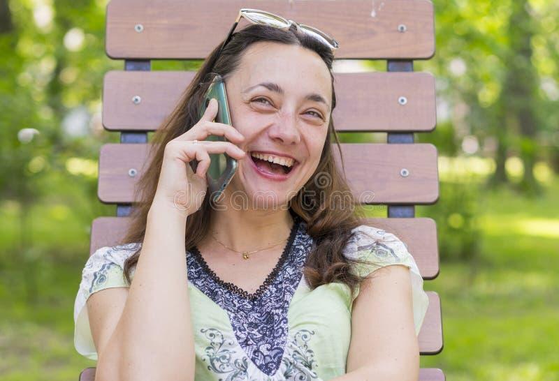 Modische moderne Schönheit, die Unterhaltungsnd-Lachen auf ihrem Mobiltelefon im Park nennt Sch?ne junge Frau, die auf Zelle spri lizenzfreie stockfotos