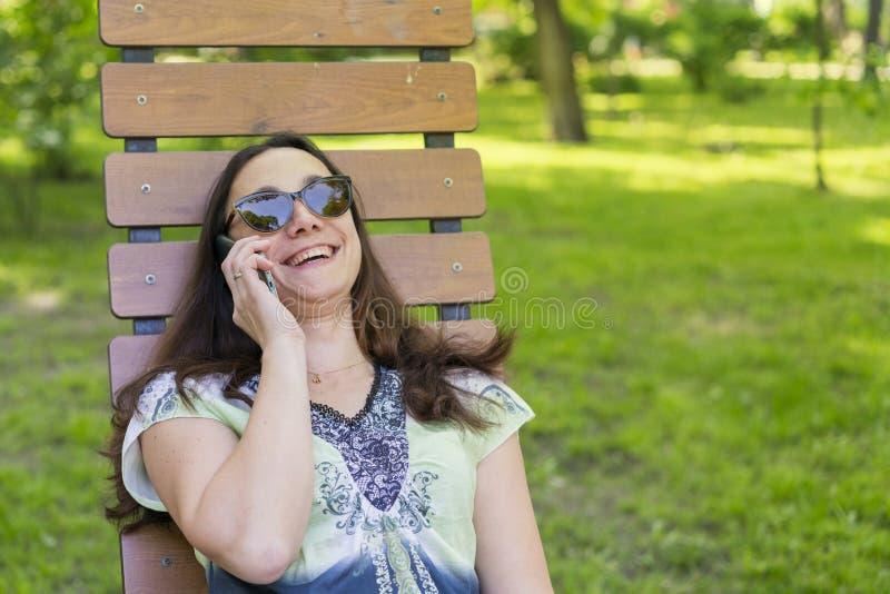 Modische moderne Sch?nheit, welche die Unterhaltung auf ihrem Mobiltelefon im Park nennt Sch?ne junge Frau, die auf Handywann spr stockbild