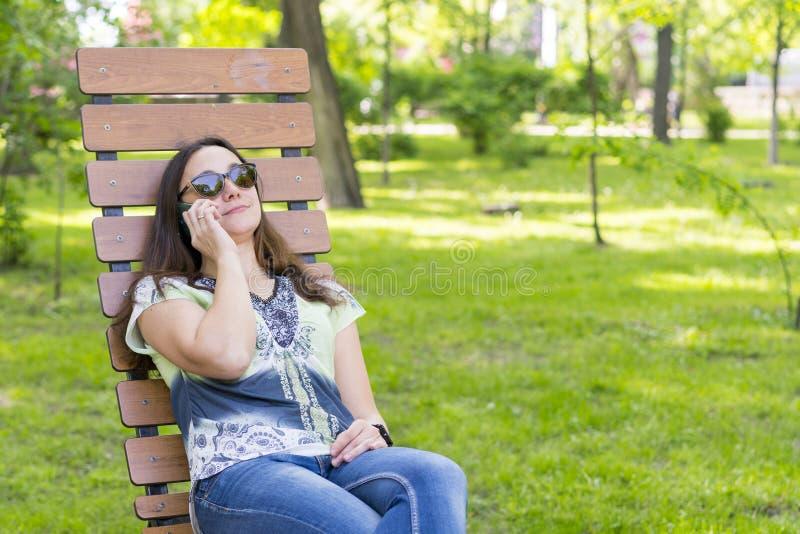 Modische moderne Sch?nheit, welche die Unterhaltung auf ihrem Mobiltelefon im Park nennt Sch?ne junge Frau, die auf Handywann spr stockbilder