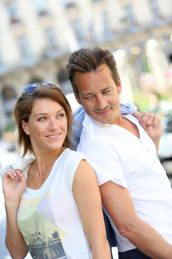 Modische Paare, die im Straßenlächeln stehen lizenzfreies stockfoto