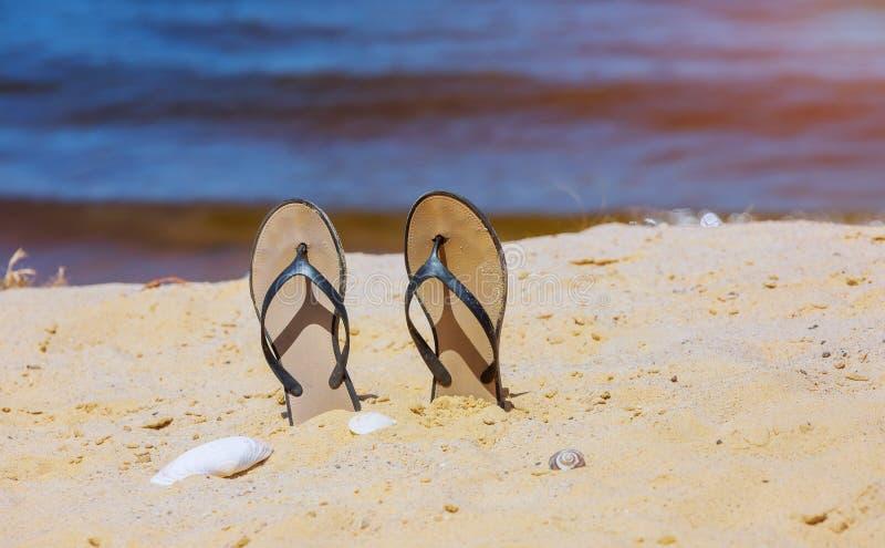Modische Pantoffel auf weißem sandigem Ozeanstrand lizenzfreie stockfotos