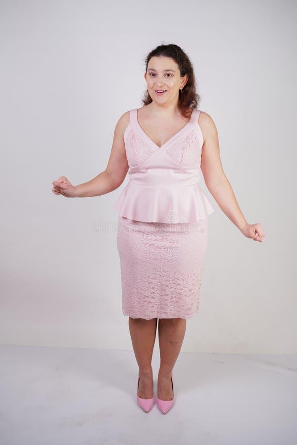 Modische pralle positive Frau mit dem Plusgrößenkörper, der im netten festen Kleid des Rosas auf weißem Studiohintergrund all lizenzfreie stockbilder