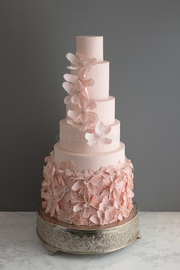 Modische rosa Hochzeitstorte mit essbaren Blumen lizenzfreies stockbild