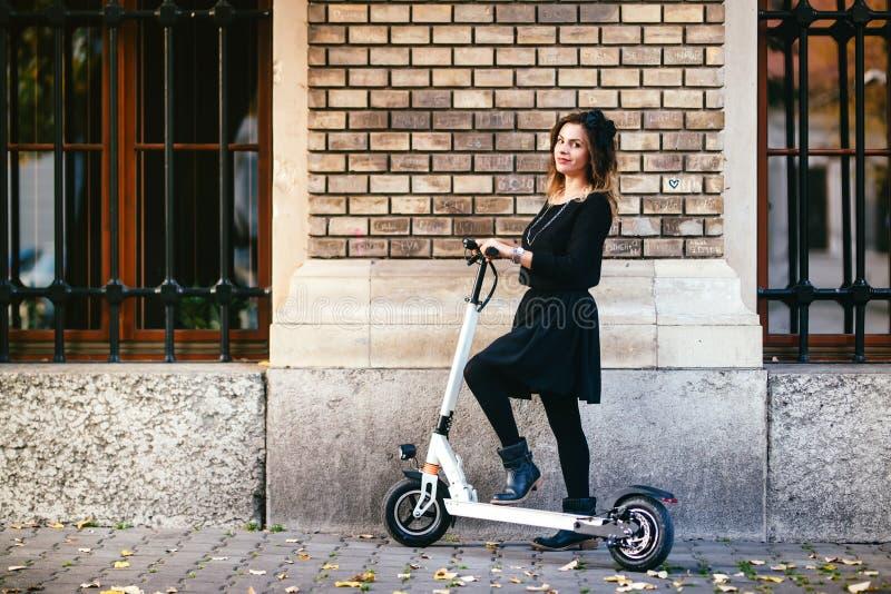 Modische sorglose Frau auf Trittroller in der Stadtlandschaft lizenzfreies stockbild