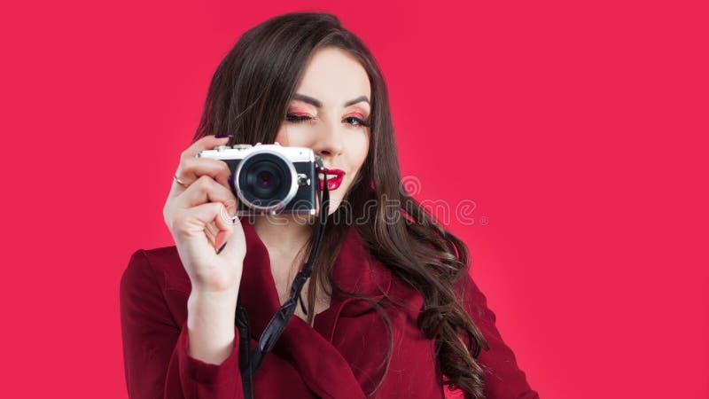 Modischer Blogger benutzen die Kamera auf rosa Hintergrund Junge Frauen mit Kamera lizenzfreie stockfotografie
